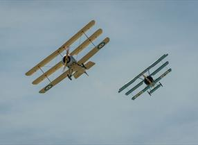Two old fashioned planes in sky