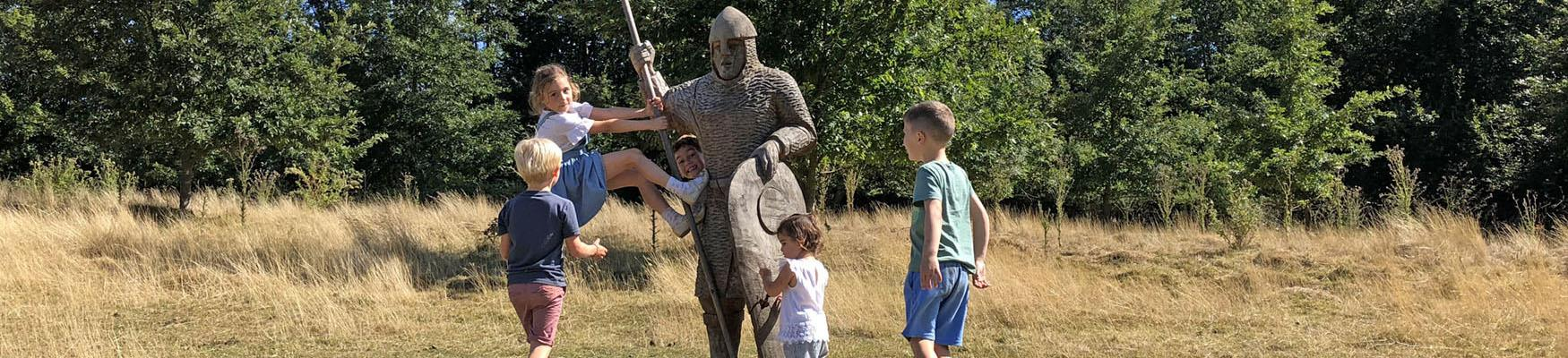 Children playing on a soldier statue