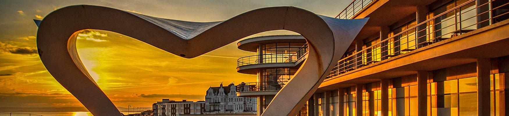 De La Warr at sunset seen through the artwork at the bandstand