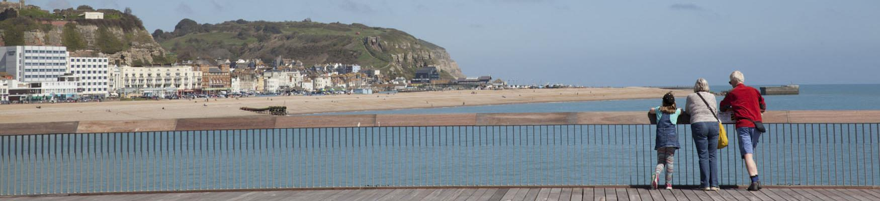 3 people standing on the pier looking at view of Hastings seaside and East hill