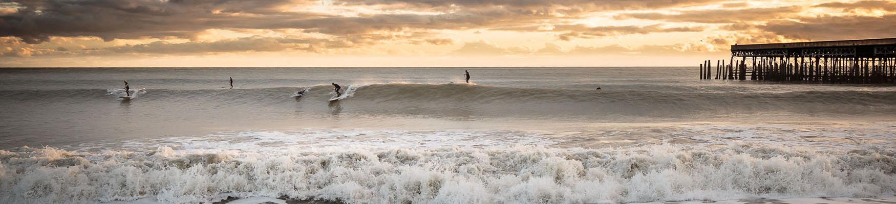 Surfers in Hastings in December by pier