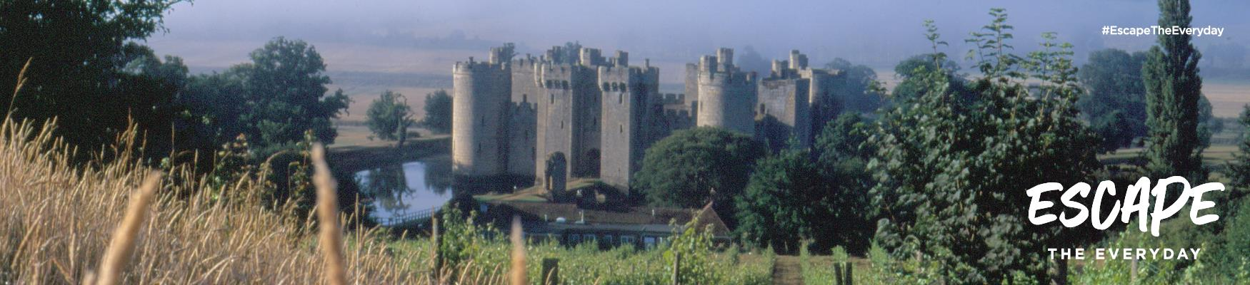 Bodiam Castle in East Sussex, viewed from a wheatfield uphill.