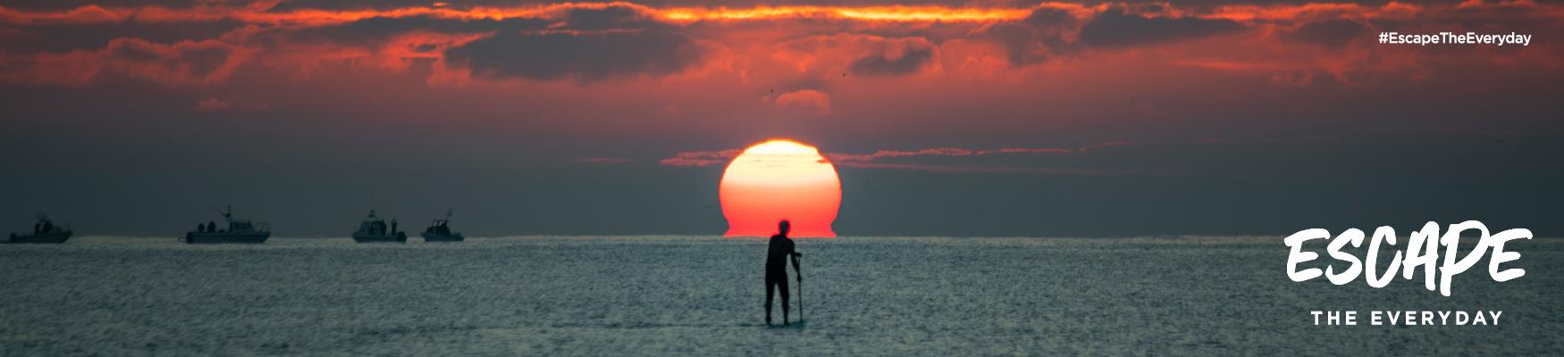 A paddleboarder on the sea with the sunset behind, on Hastings beach, East Sussex.