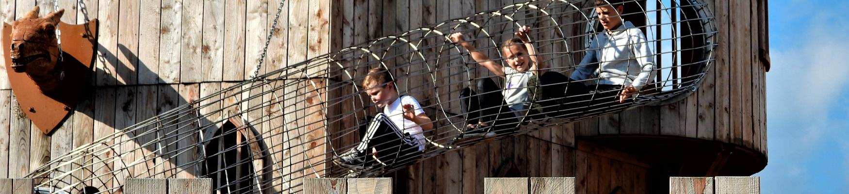 Children climbing through a metal tunnel at Knockhatch Adventure Park