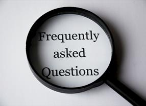 Magnifying glass showing the words 'frequently asked questions'