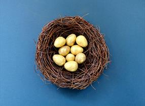 Golden eggs in a brown nest for Easter