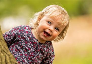 a photograph of a small white child with blonde hair smiling as they appear behind a tree trunk. background is blurred.