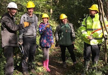 a photograph of five people stood in forest with hard hats on. man to right wears high viz jacket whilst others are young adults / teenagers.
