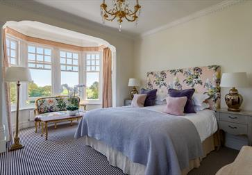 an interior photograph of a hotel bedroom at rye lodge. shows double bed with floral headrest. mauve throw, and bay windows.