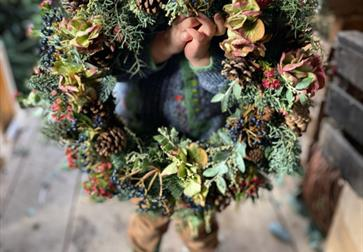 a small child holding a door wreath to the camera, their blue boots visible but their face completely hidden by the wreath.