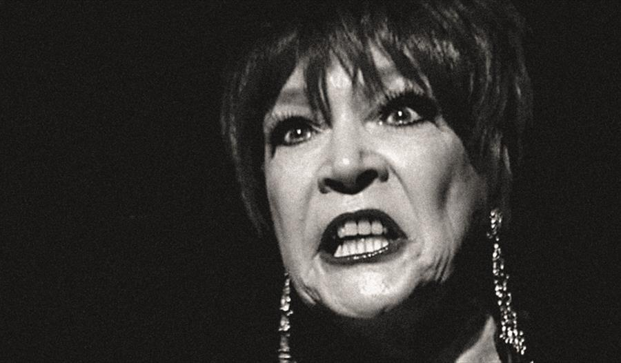 a black and white photograph, close up portrait of a woman's face with completely black background. Woman has dark lipstick and bears her teeth in an