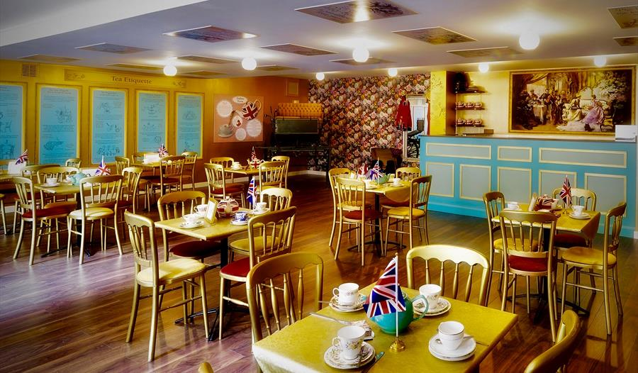 a photograph of the interior the British Tea Museum, Hastings, East Sussex. showing chairs and tables with cups and saucers, with union jack flags as