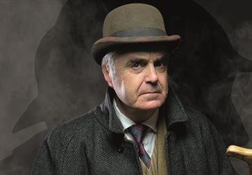 a portrait of a white man in a bowler hat, tie and coat. Background is dark and smokey.