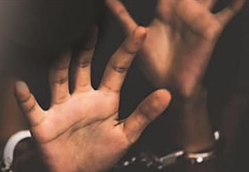 a photograph of a black person's hands reaching towards the camera with a blurred background. Handcuffs just visible.