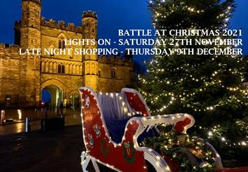 a composite photograph, with battle abbey lit up at night in the background, and a sleigh and Christmas tree in the foreground.
