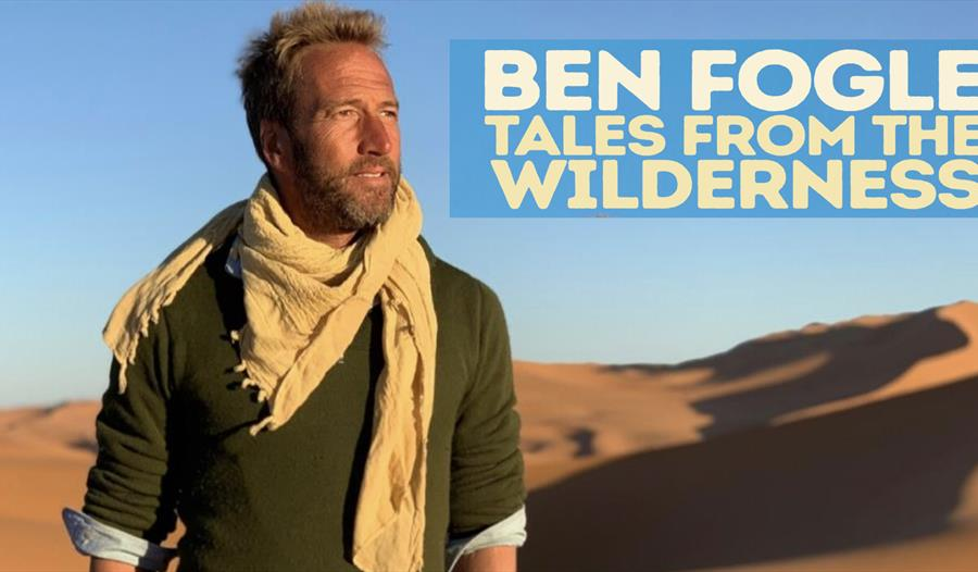 a poster for ben fogle tour at white rock. White man stands in the desert wearing a green top and biege scarf. top right text says ben fogle tales fro