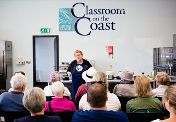 a photograph of a cookery classroom with a teacher, CJ Jackson, in the front, rows of backs of heads.