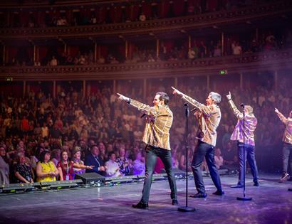 A photograph of musical theatre group Collabro performing on stage. The back of four men in gold jackets in a packed theatre. They each point to the s