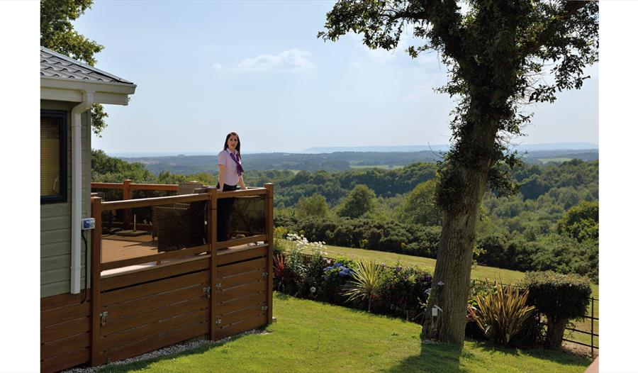 Woman standing on lodge decking enjoying the view  at Crowhurst Park East Sussex