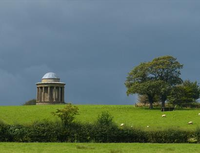 a photograph of a bright green grassy field from a distance, with dark grey moody sky. At the top of the feild is a round domed monument.
