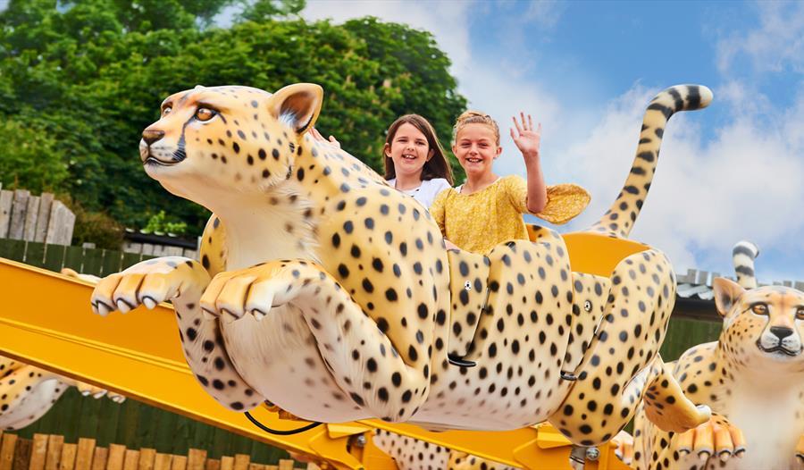 Children on a leopard funfair ride at Drusillas Park, Alfriston, East Sussex