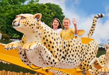 Children on a leopard funfair ride at Drusillas Park, Alfriston, East Sussex