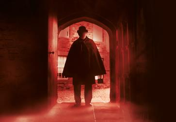 a dark photograph with a near silhouette of a man in a bowler hat and cloak as he enters through an arched wooden door. There is a red hue and a blur.