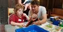A child and a man playing with Lego at Hastings Museum and Art Gallery, East Sussex