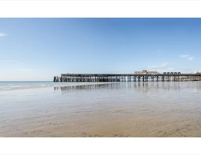Hastings Pier at low tide viewed from the beach on the eastern side