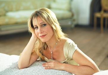 a photograph of a musician, taken from back of a sofa. A white woman with blond hair sits on floor and rests her elbows on seat of sofa, is smiling.
