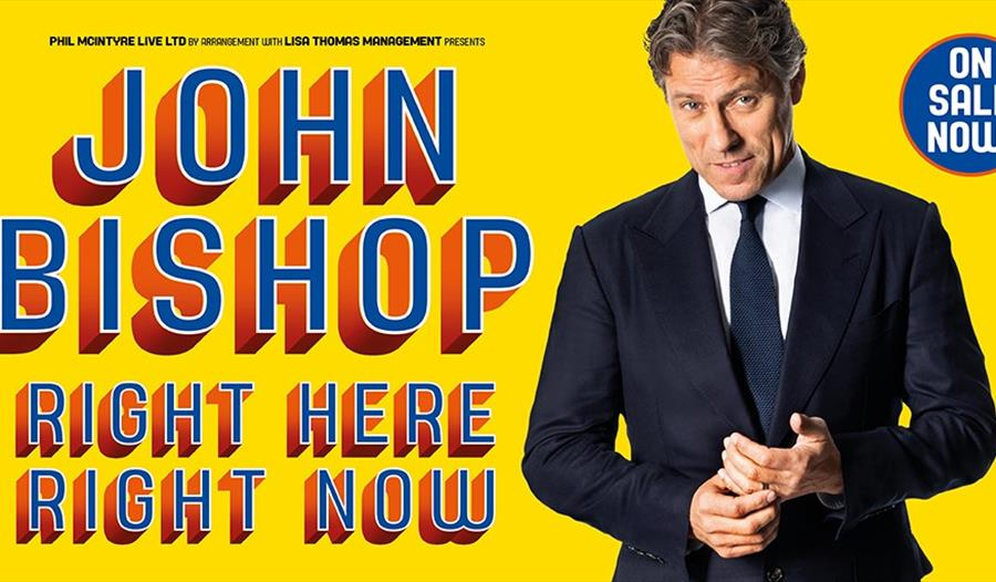 A poster with a yellow background. To the right a white man in a suite. Left says John Bishop. Right here right now.