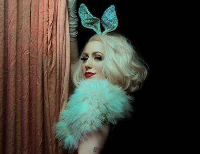 A photograph of a burlesque performer, with blonde hair and bunny ears. For an event at St Mary in the Castle Hastings