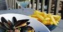 Close up of a table outside at bexhill restaurant pebbles showing a bowl of mussels, bowl of chips and glass of wine.