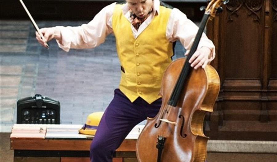 A man in a yellow waistcoat and purple trousers plays a cello on stage. For a Rye Creative Centre event, Rother.