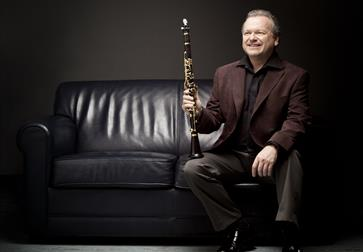 A photograph of a man sat on a black sofa with a clarinet resting on knee. Black background, man wears black suit.