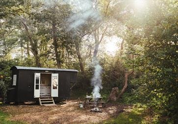 Photograph of a black glamping hut in a woods with smoking fire.