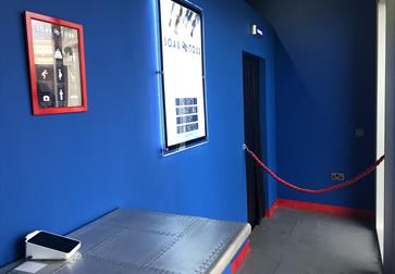 The entrance foyer to Soar Tour Bexhill, showing a blue wall, small table and illuminated poster on the wall for the attraction.