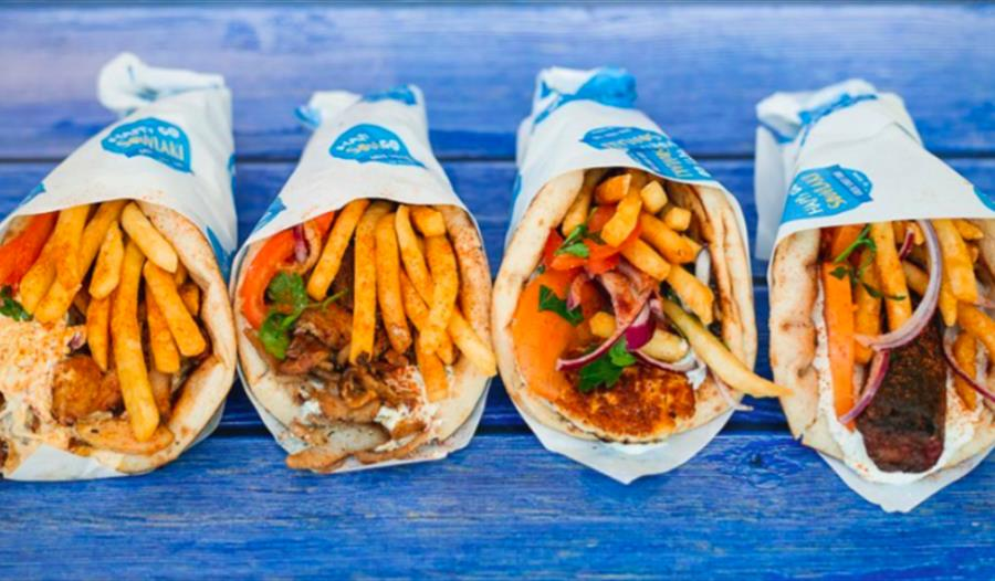 A photograph of greek takeaway food. There are four pitta wraps folded in paper in a row, against a blue backdrop.