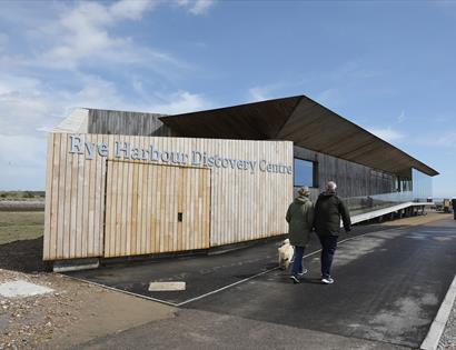 Photograph by Kt Bruce of the Rye Harbour Discover Centre. A couple wearing coats walk their dog past the wooden structure.