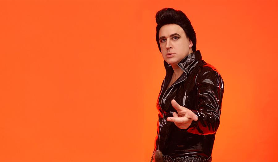 man standing before plain bright orange background. white man in leather jacket and high brown hair, like Elvis Presley.