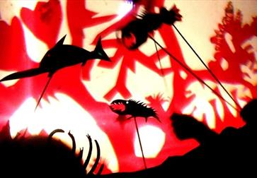 shadow puppets of underwater creatures against a red and white background.