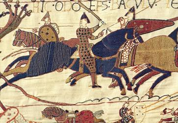 a section of the Bayeux tapestry, medieval embroidery shoes stitched image of a knight with helmets and swords on horseback.