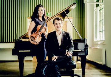 photograph of two musicians, a woman standing with violin and man seated with back against piano, green wallpaper in the background and light coming t