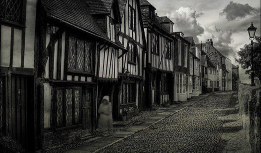 a black and white photograph of an old cobbled street and terraced houses.