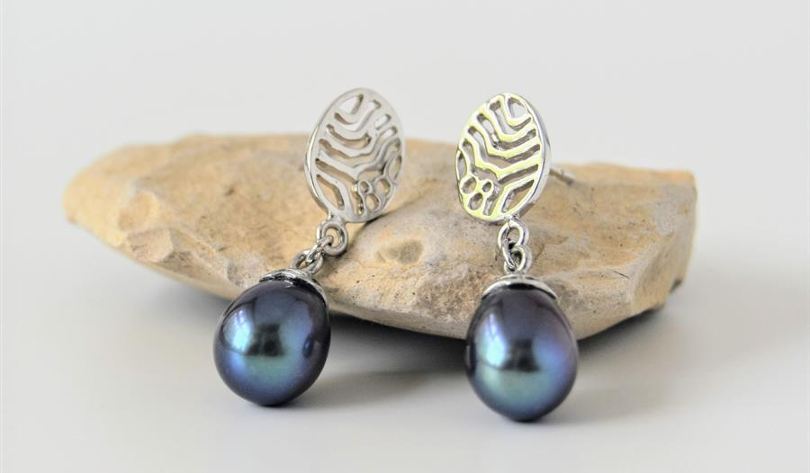a photograph of earings placed on a small light coloured stone. Silver dangling earings with blue pearlescent stone.