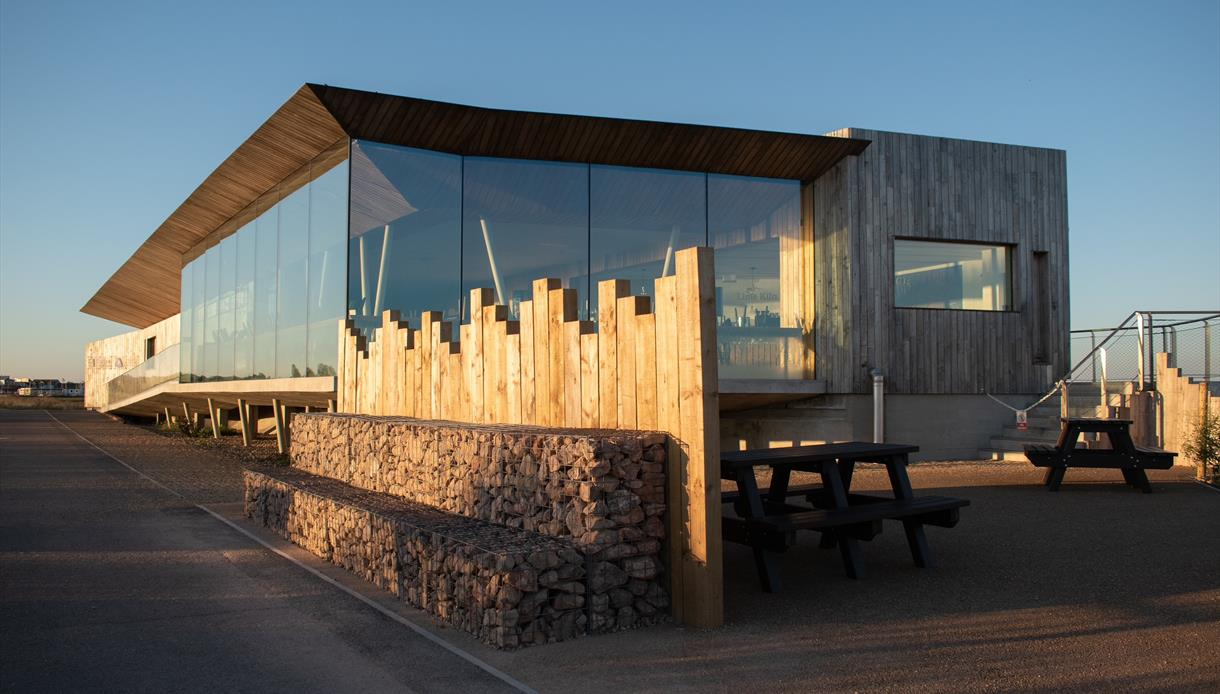 a photograph of Rye Harbour visitor centre. Wooden and glass structure against a blue sky.