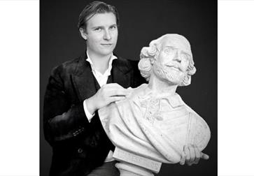 A black and white photograph of a white man holding a bust of Shakespeare.
