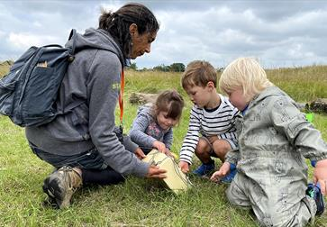 photograph of three small children playing in the grass, woman with backpack showing them a box.
