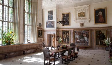The Great Hall at Parham House. Dining table and chairs in centre of room with large portraits on the wall.
