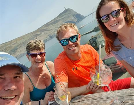 Group with drinks at a table outside Foraging Vintners Port Erin